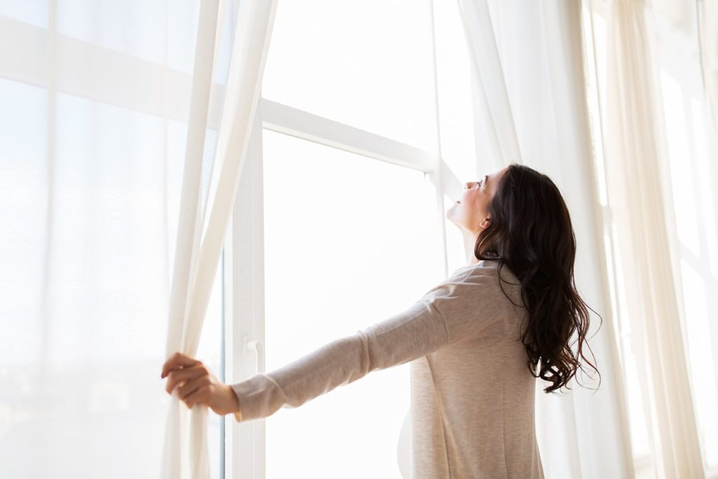 femme ouvrant ses rideaux